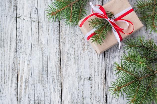Weihnachtshintergrund mit geschenk- und tannenbaum auf weißem holztisch, Premium Fotos