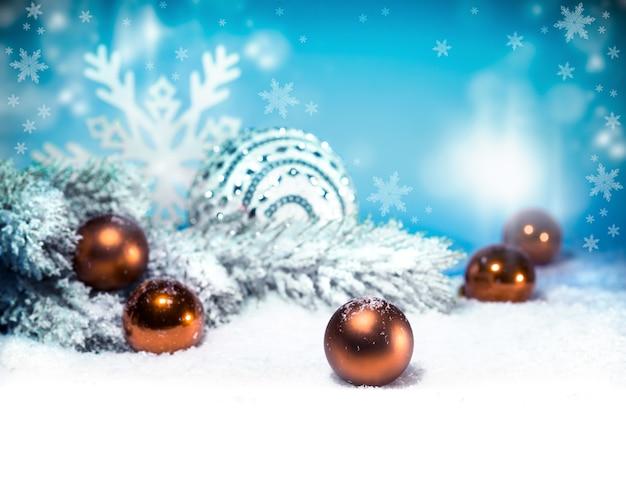 Weihnachtshintergrund mit schnee- und weihnachtsbällen Premium Fotos