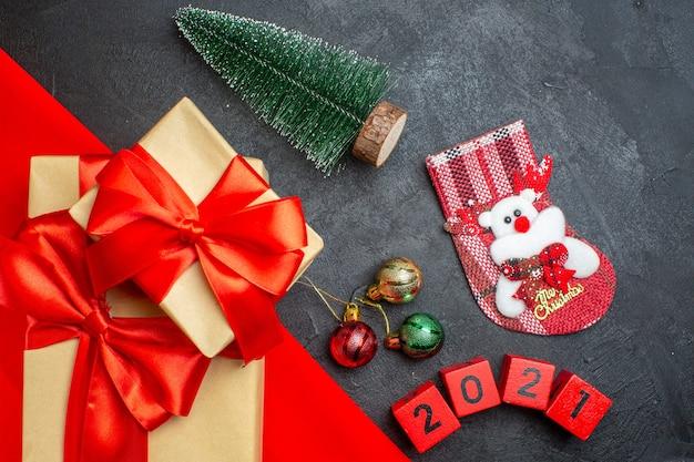 Weihnachtshintergrund mit schönen geschenken mit bogenförmigem band auf einem roten handtuch und nummerierten weihnachtssockendekorationszubehör auf einem dunklen tisch Kostenlose Fotos