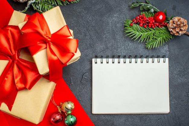 Weihnachtshintergrund mit schönen geschenken mit bogenförmigem band und notebook-tannenzweig-dekorationszubehör auf einem dunklen tisch Kostenlose Fotos