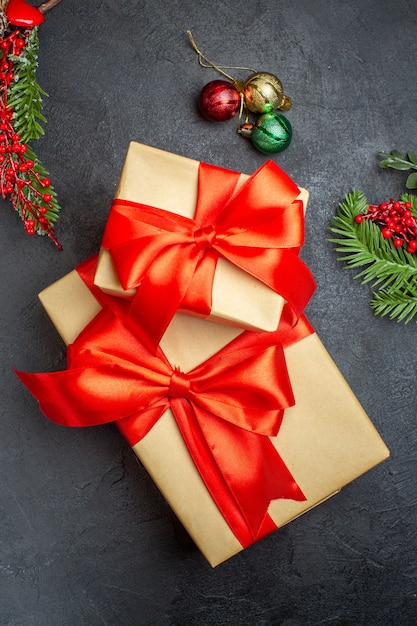 Weihnachtshintergrund mit schönen geschenken mit bogenförmigem band und tannenzweigdekorationszubehör auf einem dunklen tisch über ansicht Kostenlose Fotos