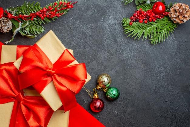 Weihnachtshintergrund mit schönen geschenken mit bogenförmigem band und tannenzweigdekorationszubehör auf einem dunklen tisch Kostenlose Fotos