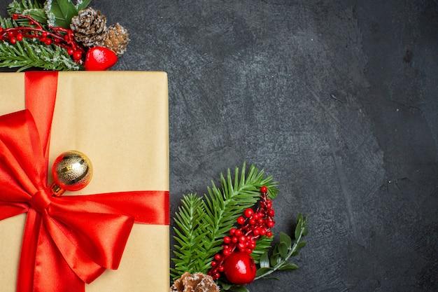Weihnachtshintergrund mit schönen geschenken mit bogenförmigem band und tannenzweigdekorationszubehör auf einem dunklen tischhälftenfoto Kostenlose Fotos