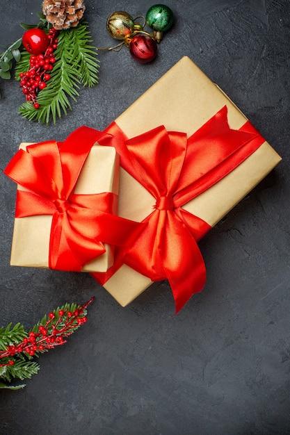 Weihnachtshintergrund mit schönen geschenken mit bogenförmigem band und tannenzweigdekorationszubehör auf einer vertikalen ansicht des dunklen tisches Kostenlose Fotos