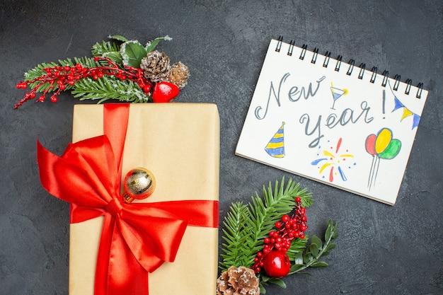 Weihnachtshintergrund mit schönen geschenken mit bogenförmigem band und tannenzweigdekorationszubehör und notizbuch auf einem dunklen tisch über ansicht Kostenlose Fotos