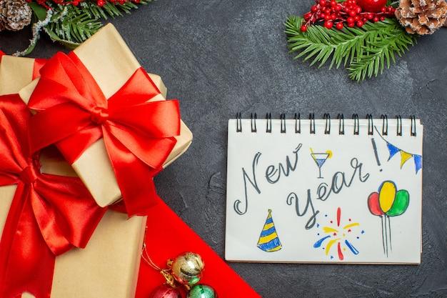 Weihnachtshintergrund mit schönen geschenken mit bogenförmigem band und tannenzweigdekorationszubehörnotizbuch auf einem dunklen tisch Kostenlose Fotos