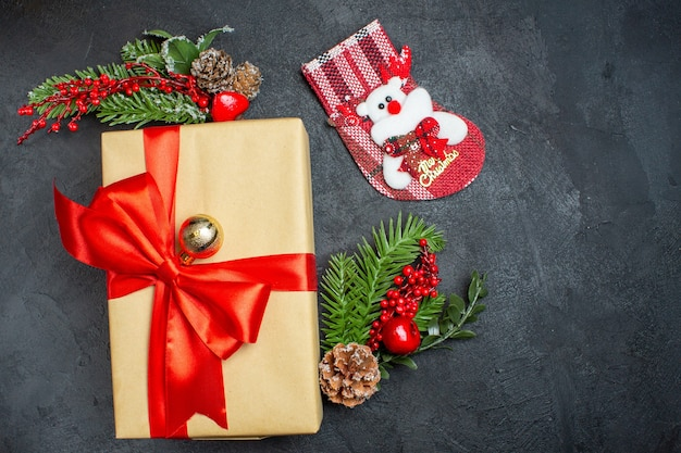 Weihnachtshintergrund mit schönen geschenken mit bogenförmigem band und tannenzweigdekorationszubehörweihnachtssocke auf einem dunklen tisch v Kostenlose Fotos