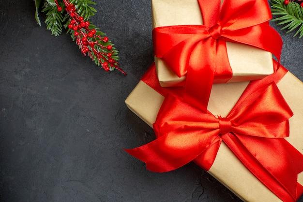 Weihnachtshintergrund mit schönen geschenken mit bogenförmigem band und tannenzweigen auf einem dunklen tisch Kostenlose Fotos