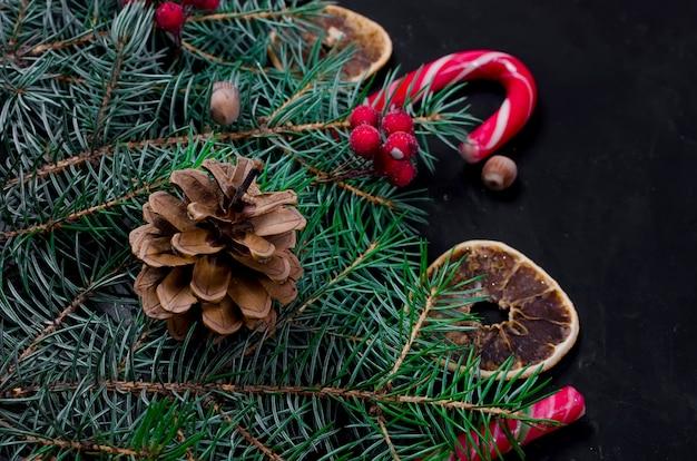 Weihnachtshintergrund mit tanne, trockene kandierte früchte, süßigkeitsstöcke Premium Fotos
