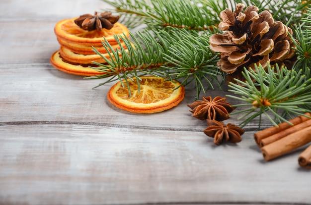 Weihnachtshintergrund mit tannenzweigen, gewürzen und getrockneten orangen. Premium Fotos