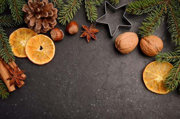 Weihnachtshintergrund mit tannenzweigen, kegeln, nüssen und scheiben der getrockneten orange. Premium Fotos