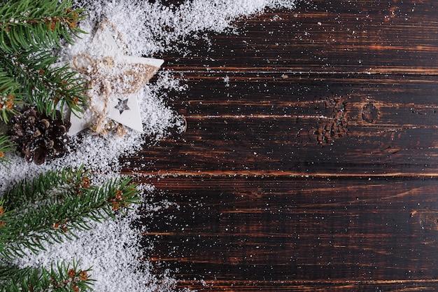 Weihnachtshintergrund, -tannenbäume und -kegel auf einem holztisch, zerquetscht durch weißen schnee, kopienraum, draufsicht. Premium Fotos