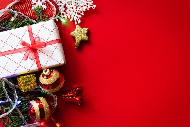 Weihnachtshintergrund. weihnachtsgeschenkbox mit roten ball- und kiefernkegeln auf rotem hintergrund. Premium Fotos