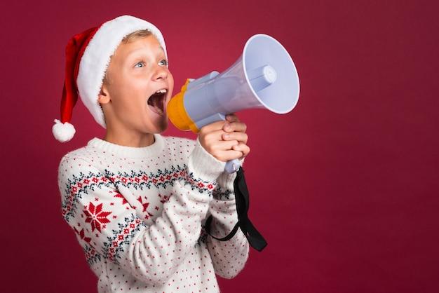 Weihnachtsjunge, der durch megaphon schreit Kostenlose Fotos