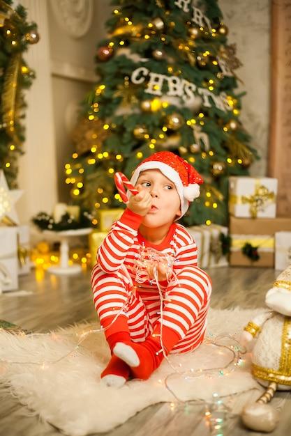 Weihnachtsjunge mit roter zuckerstange und sankt-hut Premium Fotos