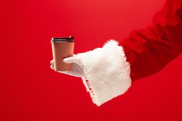 Weihnachtskaffee. die santa hand hält tasse kaffee lokalisiert auf einem roten Kostenlose Fotos