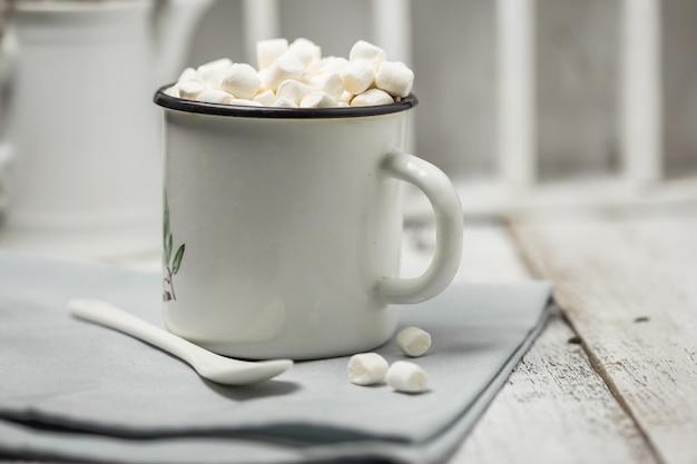 Weihnachtskakaogetränk. schokoladen-kakao-getränke mit marshmallows im weißen weihnachtsbecher auf grauer wand. traditionelles heißgetränk, festlicher cocktail zu weihnachten oder neujahr Premium Fotos