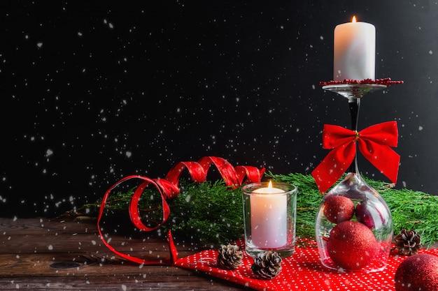 Weihnachtskerze auf einem umgekehrten glas, fichtenzweigen und weihnachtsdekorationen Premium Fotos