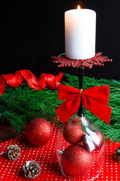 Weihnachtskerze auf umgekehrtem glas, fichtenzweigen und weihnachtsdekorationen desi Premium Fotos