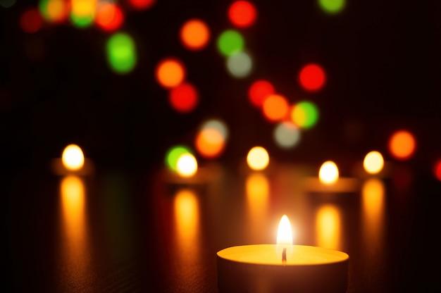 Weihnachtskerzen entzünden romantische dekoration des lichtes in defocused lichtern Premium Fotos