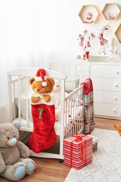 Weihnachtskinderzimmer, kinderspielzimmer für neujahr dekoriert, weißes kinderzimmer, weihnachtsspielzeug und geschenke im kinderzimmer, weißes bett mit stofftieren Premium Fotos