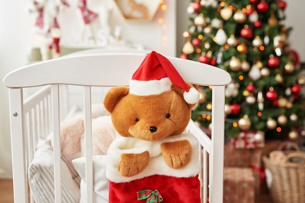 Weihnachtskinderzimmer, weihnachtsdekoration im kinderzimmer, kinderspielzimmer für neujahr dekoriert, weißes kinderzimmer. weihnachtsspielwaren und -geschenke im schlafzimmer der kinder, weißes bett mit weichen spielwaren Premium Fotos