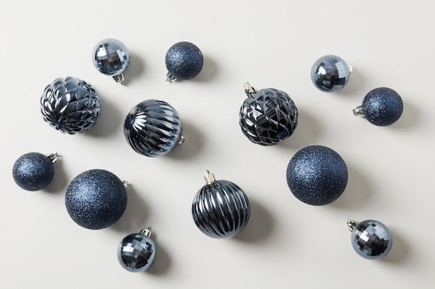 Weihnachtsklassische blaue bälle auf pastellgrau. ansicht von oben. weihnachtsmuster. feiertagsgrußkarte. Premium Fotos