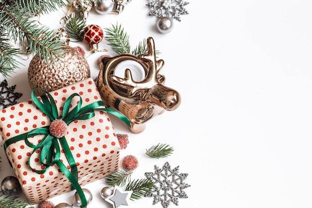 Weihnachtskomposition. geschenke, tannenzweige, rote verzierungen an weißer wand. winter, neujahrskonzept. flach gelegt, isometrisch, platz für text Kostenlose Fotos