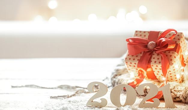 Weihnachtskomposition mit hölzernen neujahrsnummer 2021 und geschenkbox auf hintergrund Premium Fotos