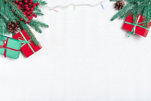 Weihnachtskomposition. weihnachtsgeschenke, tannenzweige, weihnachtslicht, girlande auf weißem hintergrund. draufsicht. Premium Fotos
