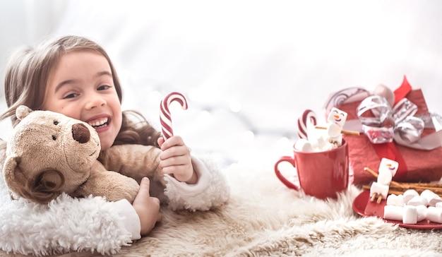 Weihnachtskonzept, kleines niedliches mädchen, das teddybärspielzeug im wohnzimmer mit geschenken auf hellem hintergrund umarmt, platz für text Kostenlose Fotos