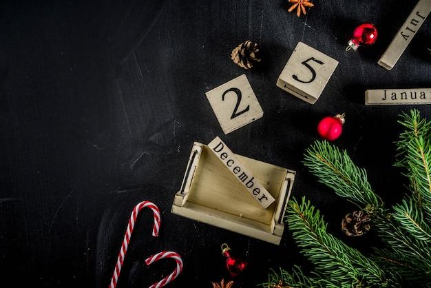 Weihnachtskonzept mit dekorationen, tannenbaumaste, mit kalender am 25. dezember Premium Fotos
