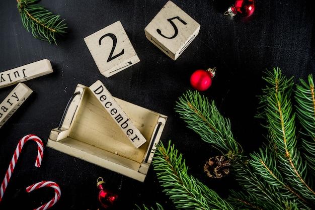 Weihnachtskonzept mit dekorationen, tannenbaumaste, mit kalender dezember p25 Premium Fotos