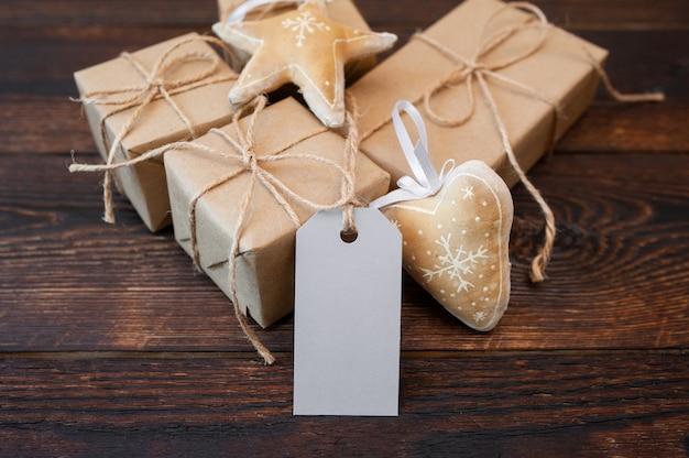 Weihnachtskraftpapier-geschenkboxen mit tag auf hölzernem Premium Fotos