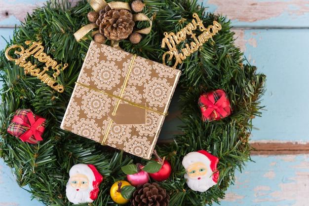 Weihnachtskranz und goldene retro- geschenkboxdekoration auf blauem hölzernem hintergrund des schmutzes Premium Fotos