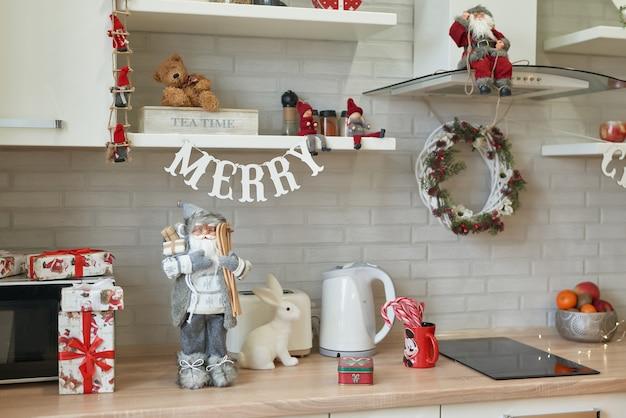 Weihnachtsküche im loftstil, kochutensilien. helle innenküche mit weihnachtsdekor und baum. modernes küchendesign, weiße küchenmöbel. weihnachtsstimmung. Premium Fotos
