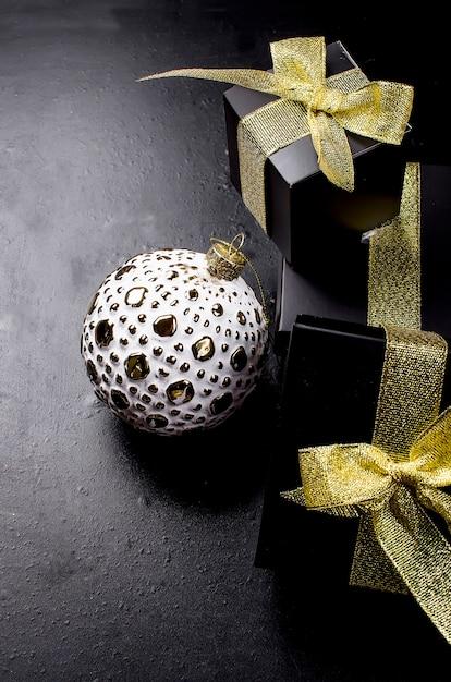 Weihnachtskugel und schwarze geschenkbox mit goldband auf schwarzem hintergrund. Premium Fotos