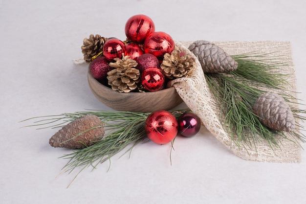 Weihnachtskugeln und tannenzapfen auf weißer oberfläche Kostenlose Fotos
