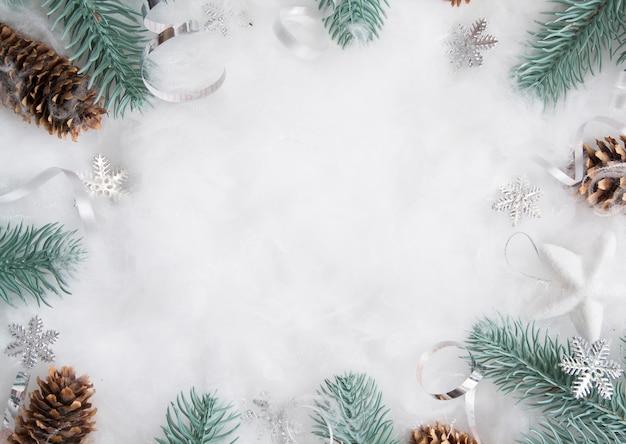 Weihnachtslayout von tannenzweigen und dekor im schnee mit einem kopierraum. winterferien flach liegen Premium Fotos