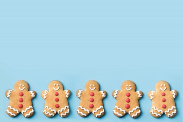 Weihnachtslebkuchenmannplätzchen auf blauer tabelle. sicht von oben. festliches feiertagslebensmittelmuster. copyspace. Premium Fotos