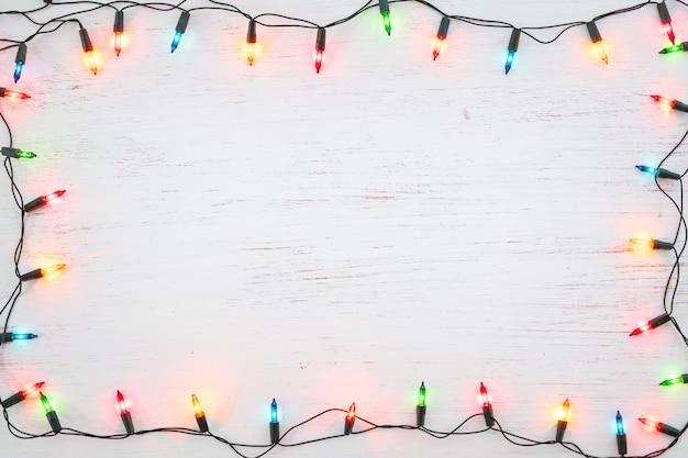 Weihnachtslichtbirnen-rahmendekoration auf weißem holz. frohe weihnachten und neujahr Premium Fotos