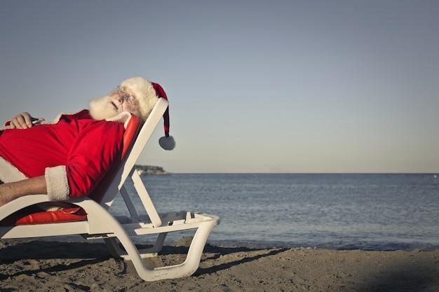 Weihnachtsmann am strand entspannen Premium Fotos