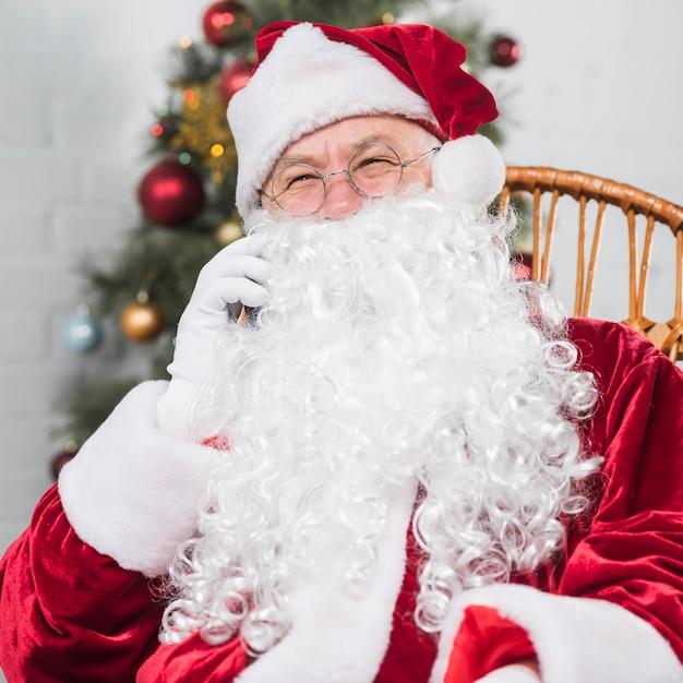 Weihnachtsmann, der auf schaukelstuhl sitzt und telefonisch spricht Kostenlose Fotos