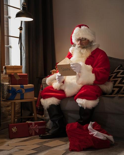 Weihnachtsmann, der einen brief von einem kind öffnet Kostenlose Fotos