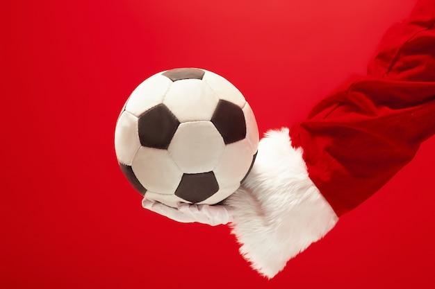 Weihnachtsmann, der einen fußballball lokalisiert auf rotem studiohintergrund hält Kostenlose Fotos