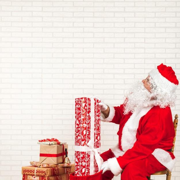 Weihnachtsmann, der geschenke in tasche einsetzt Kostenlose Fotos