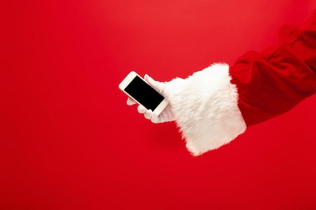 Weihnachtsmann, der handy bereit hält für weihnachtszeit auf rotem studiohintergrund. die jahreszeit, winter, feiertag, feier, geschenkkonzept Kostenlose Fotos