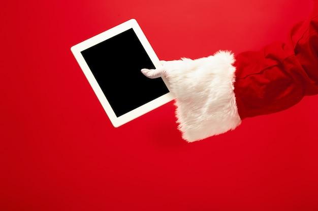 Weihnachtsmann, der laptop bereit für weihnachtszeit auf rotem studiohintergrund hält. die jahreszeit, feiertag, feier, geschenkkonzept Kostenlose Fotos