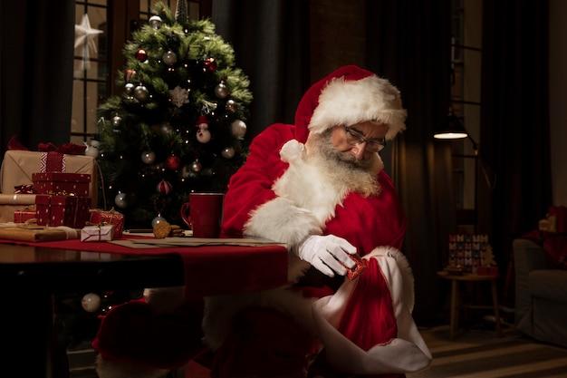 Weihnachtsmann, der weihnachtsgeschenke vorbereitet Kostenlose Fotos