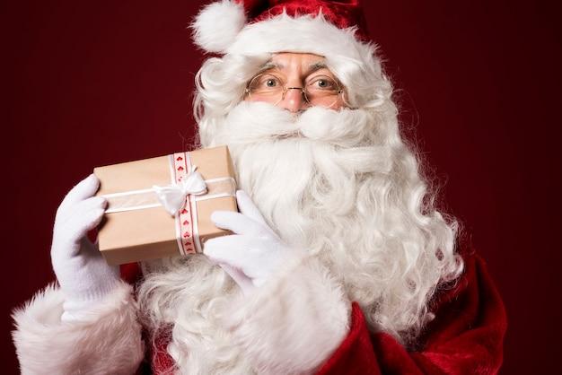 Weihnachtsmann hält eine geschenkbox Kostenlose Fotos